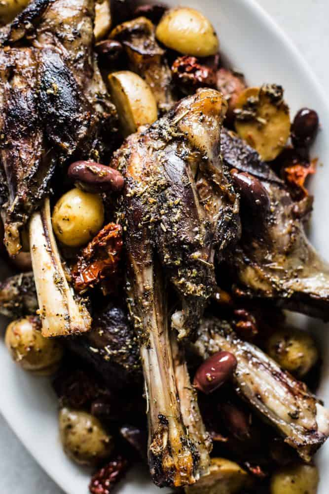 Close-up of Slow Cooker Greek Lamb Shanks on a white plate.