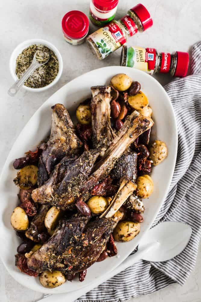 Slow Cooker Greek Lamb Shanks on a white platter with McCormick seasonings.