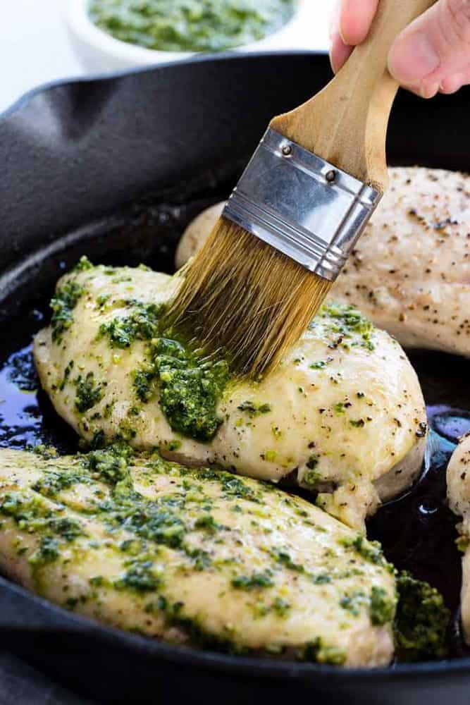 Brushing pesto sauce on chicken breasts.