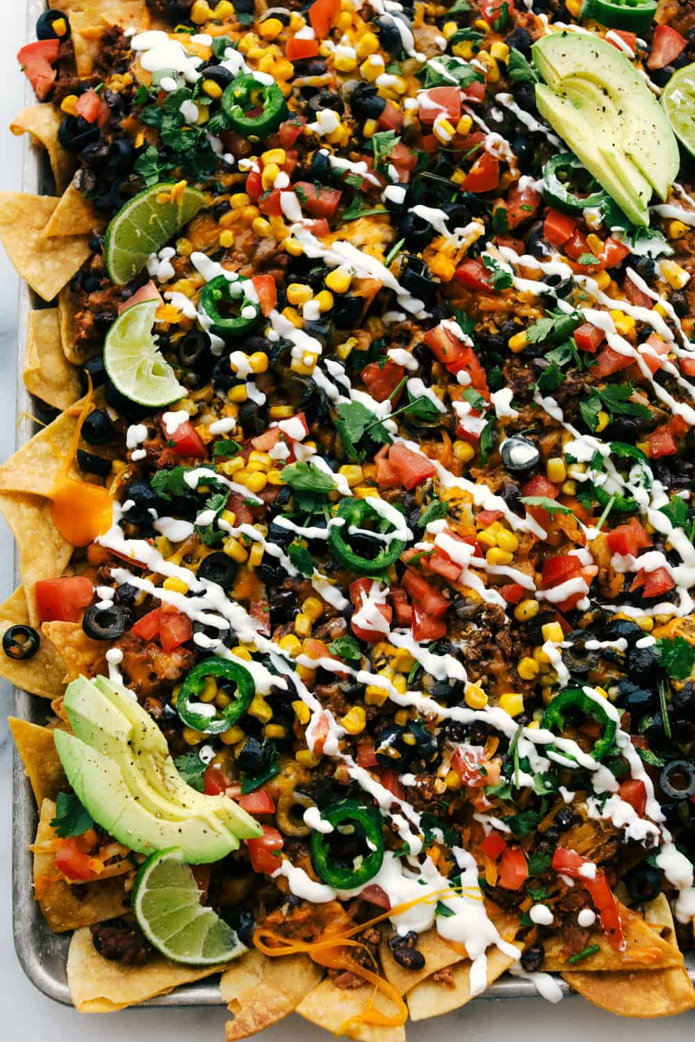 Oven baked sheet pan nachos with sour cream and avocado over top.