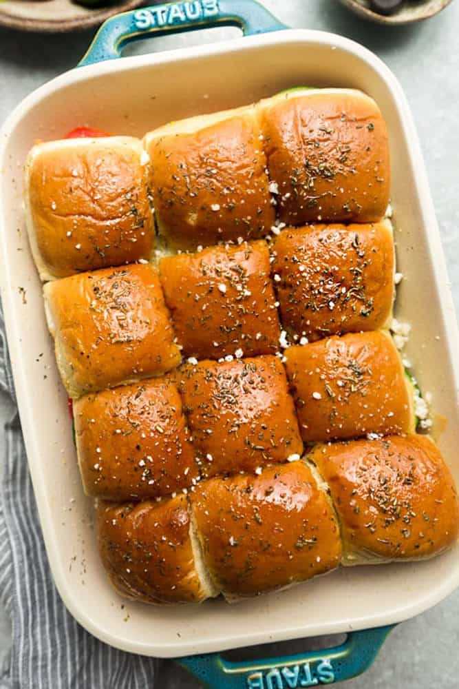 Greek Chicken Sliders in a white iron pan.