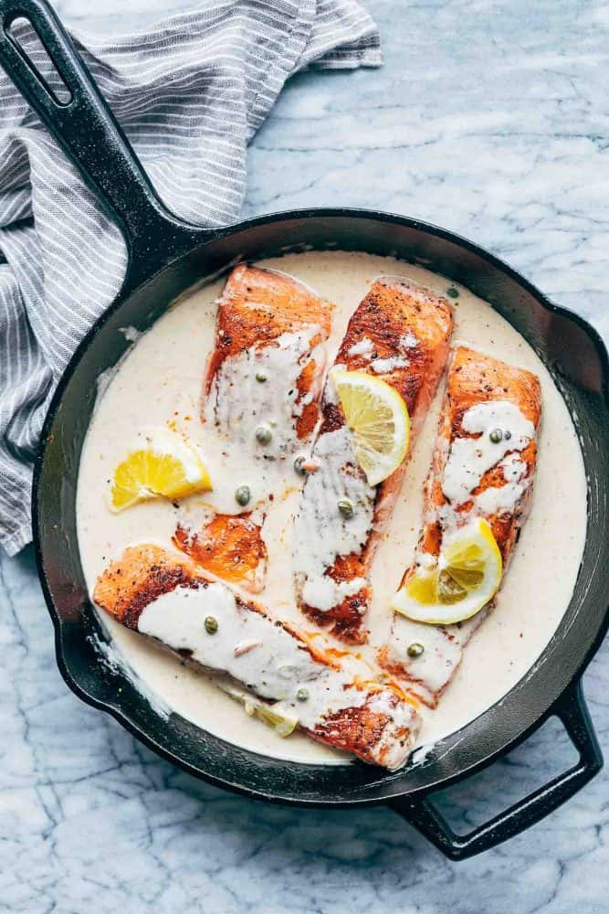 Lemon Salmon Piccata served in a cast iron pan with creamy sauce and lemon slices drizzled all over it