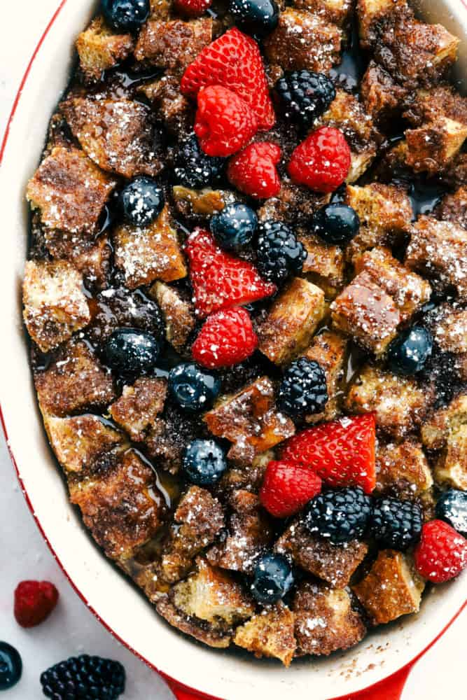 Baked French toast in a pan with fresh raspberries, strawberries and blueberries over top.