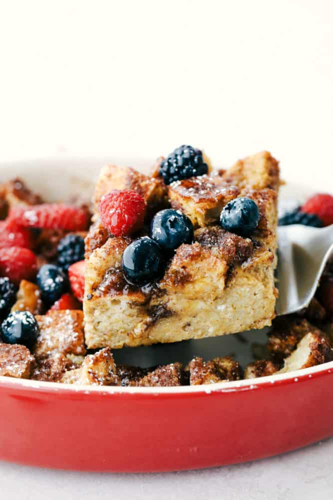 A slice of baked French toast on a spatula with fresh fruit on top.