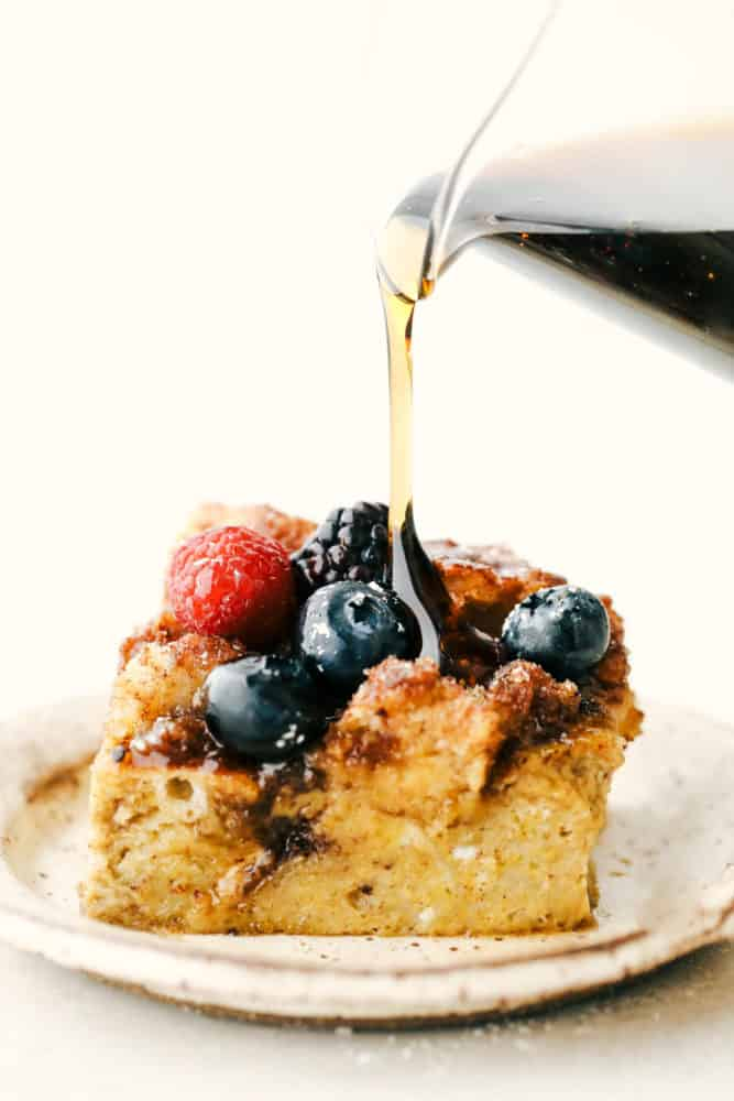 Baked French toast slice on a plate with syrup being poured overtop.