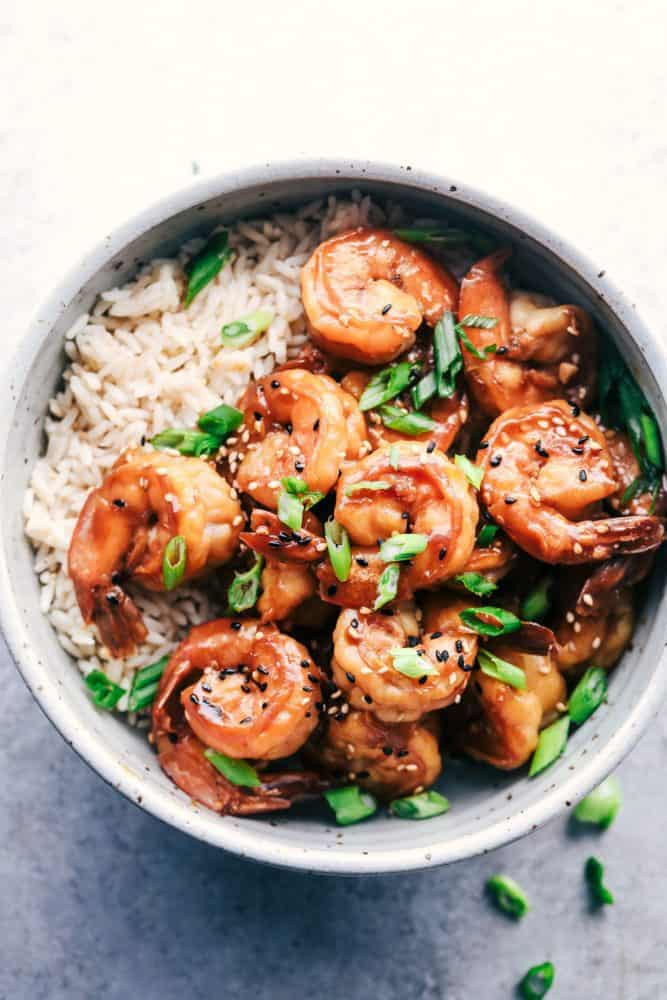 Sticky Sesame Garlic Shrimp over white rice in a white bowl.