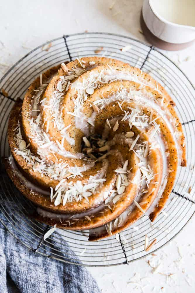 Bundt cake on a cooling rack with almond slices on top.