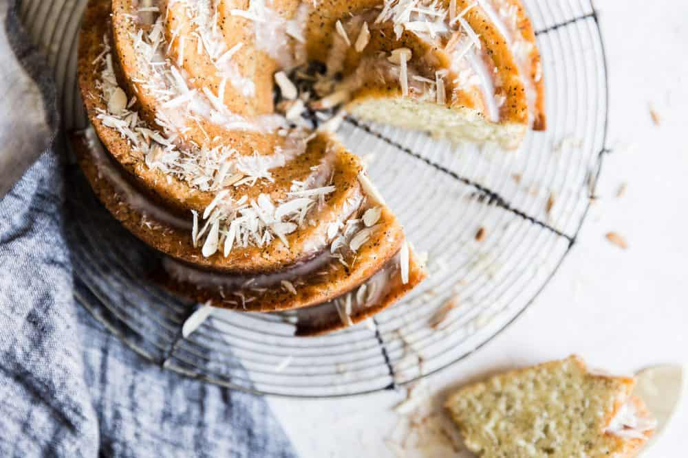 Almond poppyseed bundt cake with a slice removed. The cake is placed on a cooling rack.