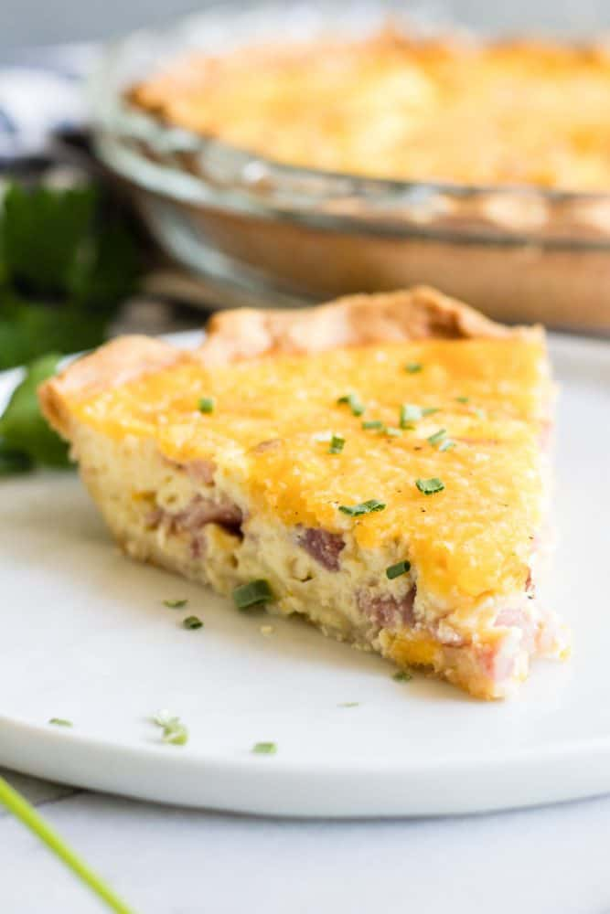 A slice of Ham and Cheese Quiche on a white plate.