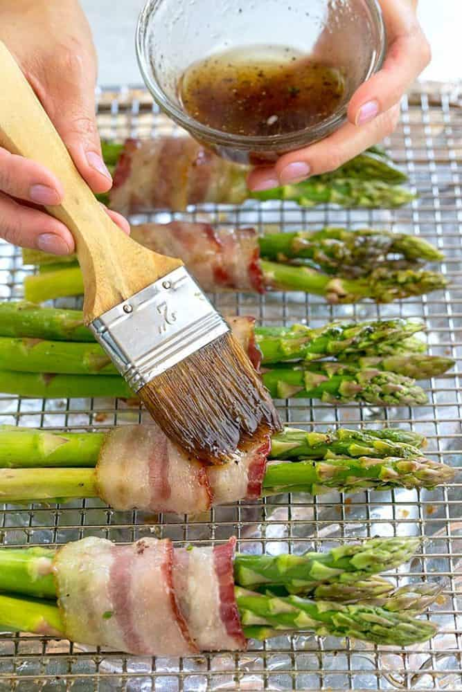 Brushing an olive oil and maple glaze over bacon wrapped asparagus.