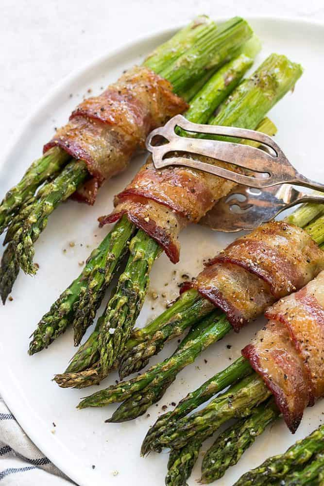 Metals tongs picking up bacon wrapped asparagus off a serving platter.