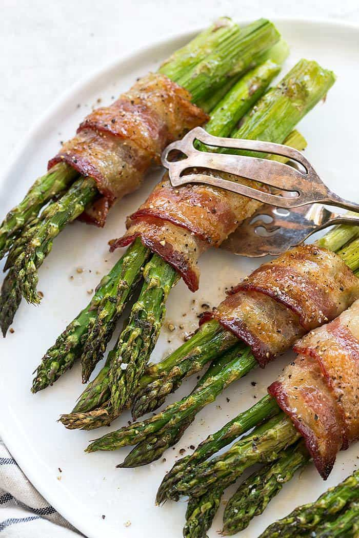 Metals tongs picking up bacon wrapped asparagus off a serving platter