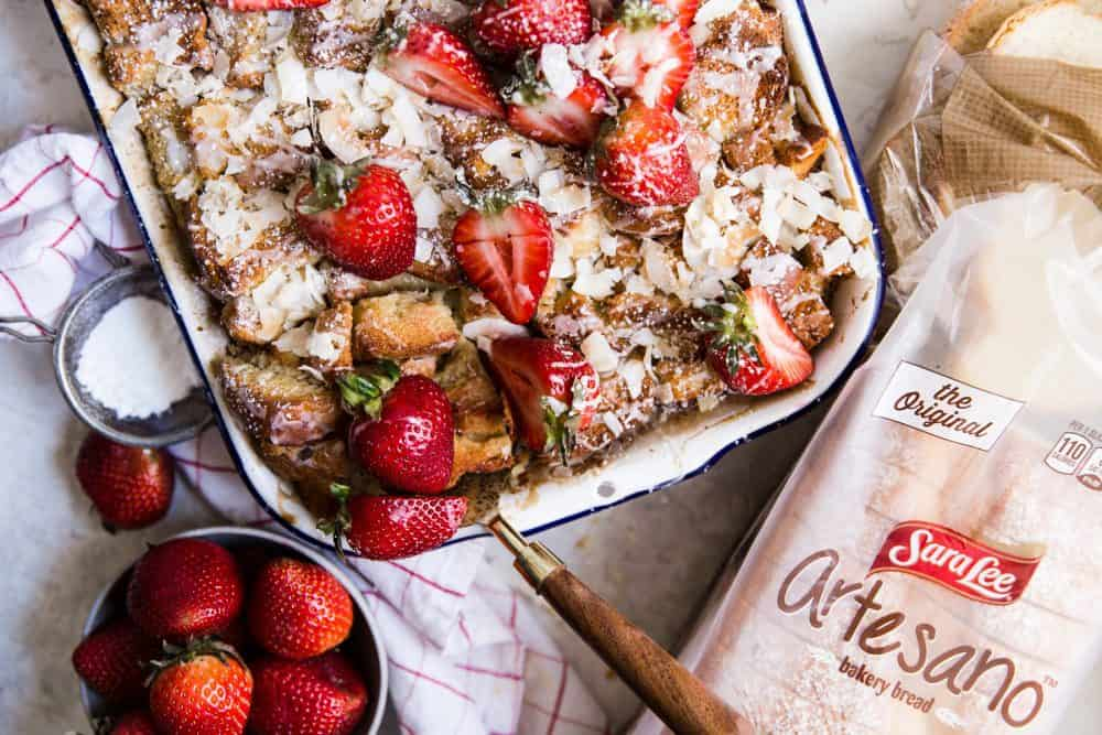 Coconut bread pudding in a white pan with fresh cut strawberries on the side and on top of the pudding. There is a loaf of SarahLee Bread next to the pan.