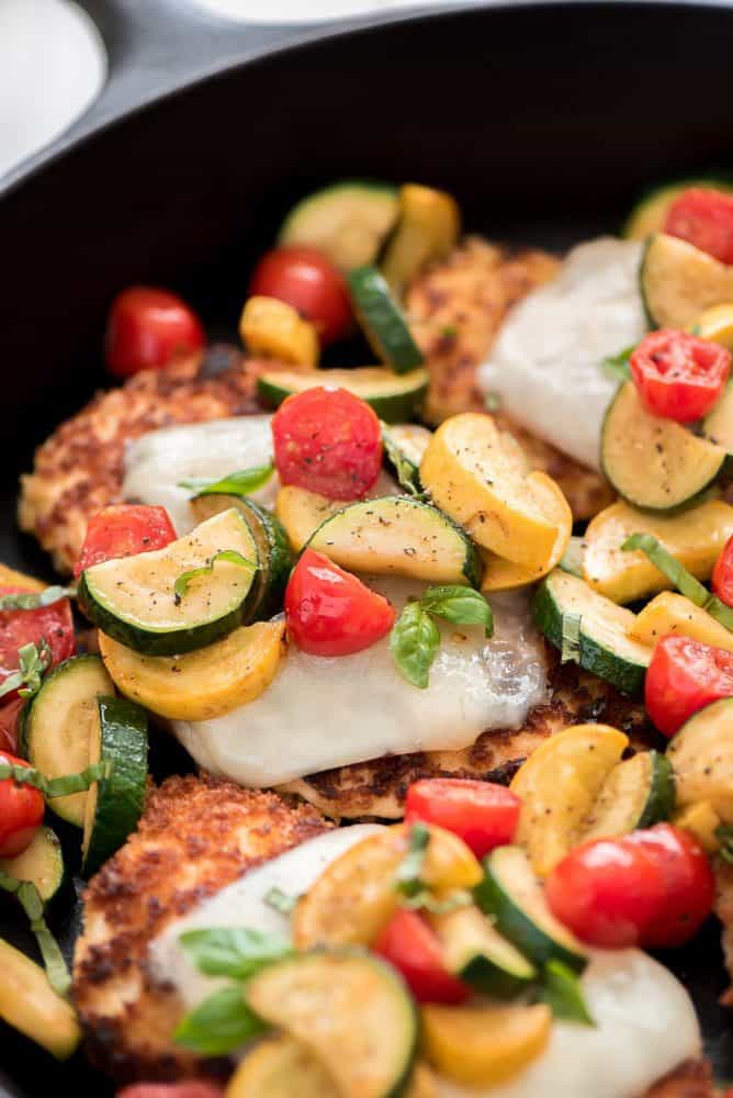 Close up of chicken parmesan with fresh cut vegetables in a skillet.