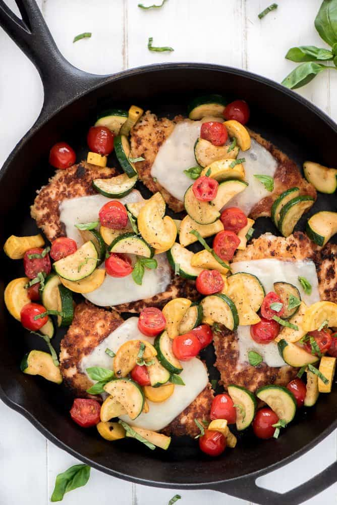 Chicken parmesan with fresh cut vegetables in a skillet.