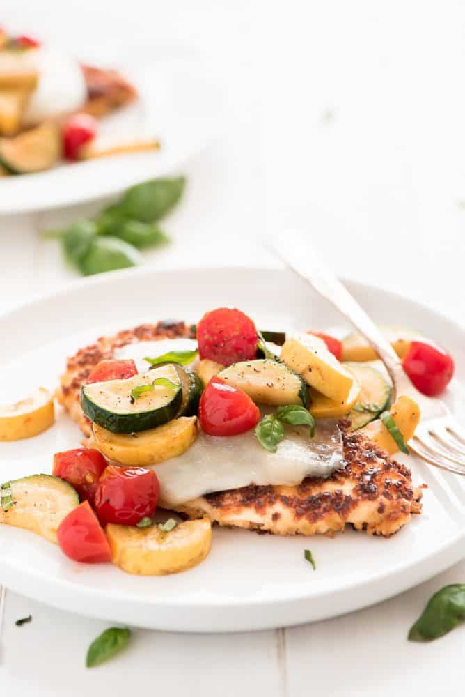 Chicken parmesan on a white plate with mixed fresh vegetables on top.