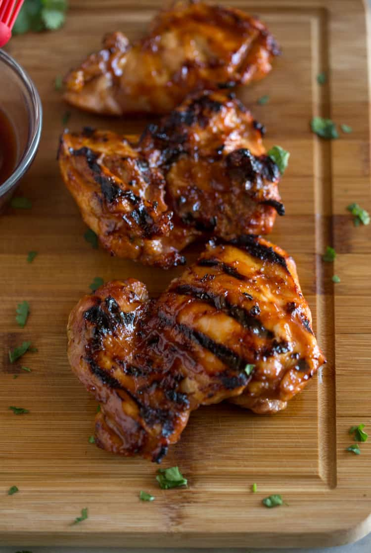 Grilled BBQ chicken thighs resting on a wood cutting board.