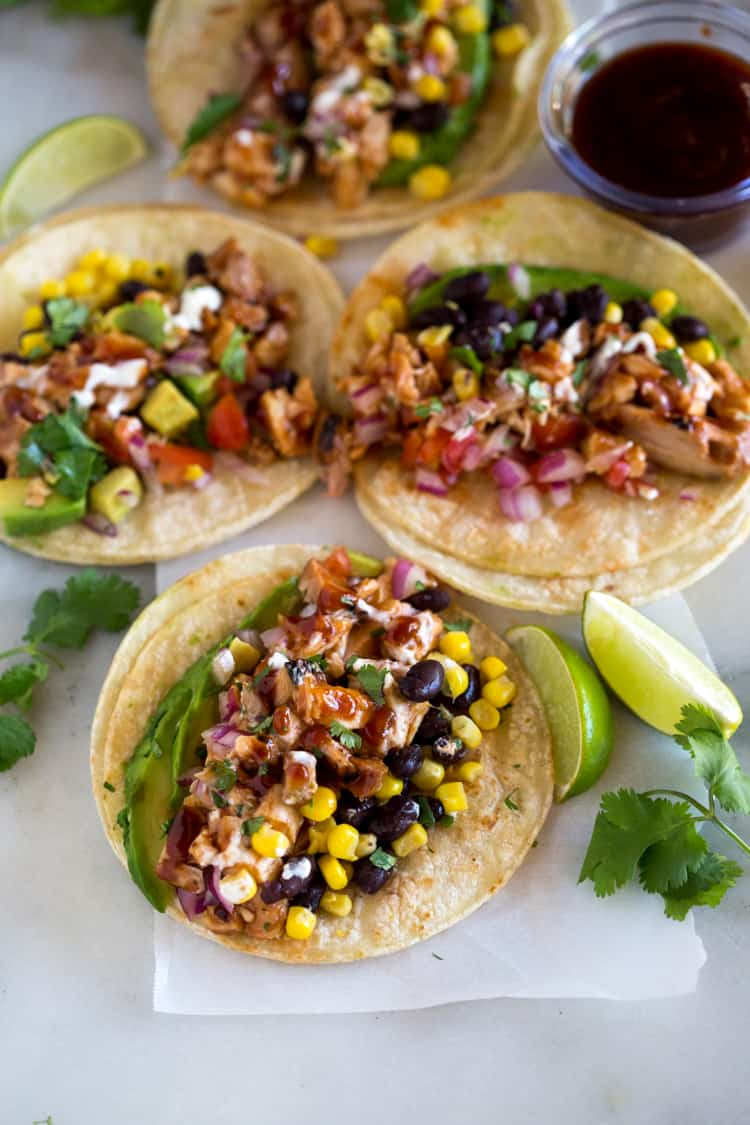 The ingredients for bbq chicken tacos piled on flat corn tortillas, including chicken, avocado, black beans, corn, and onion, with lime wedges and cilantro on the side.