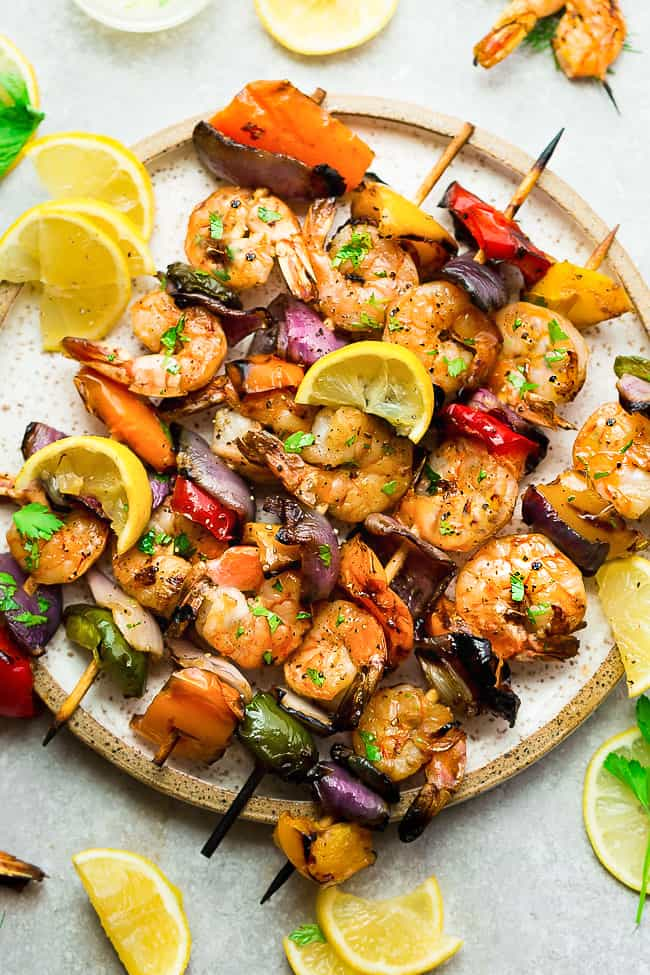 Grilled Lemon Garlic Butter Shrimp with Vegetables on a white plate.