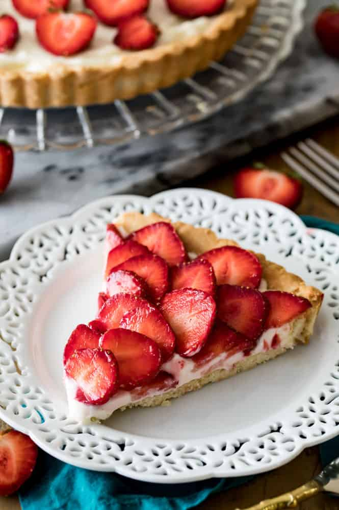 One slice of Strawberry Tart on a white decorative plate.