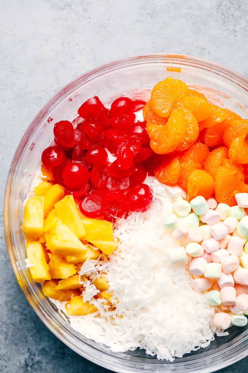 Ambrosia Salad ingredients in a glass bowl.