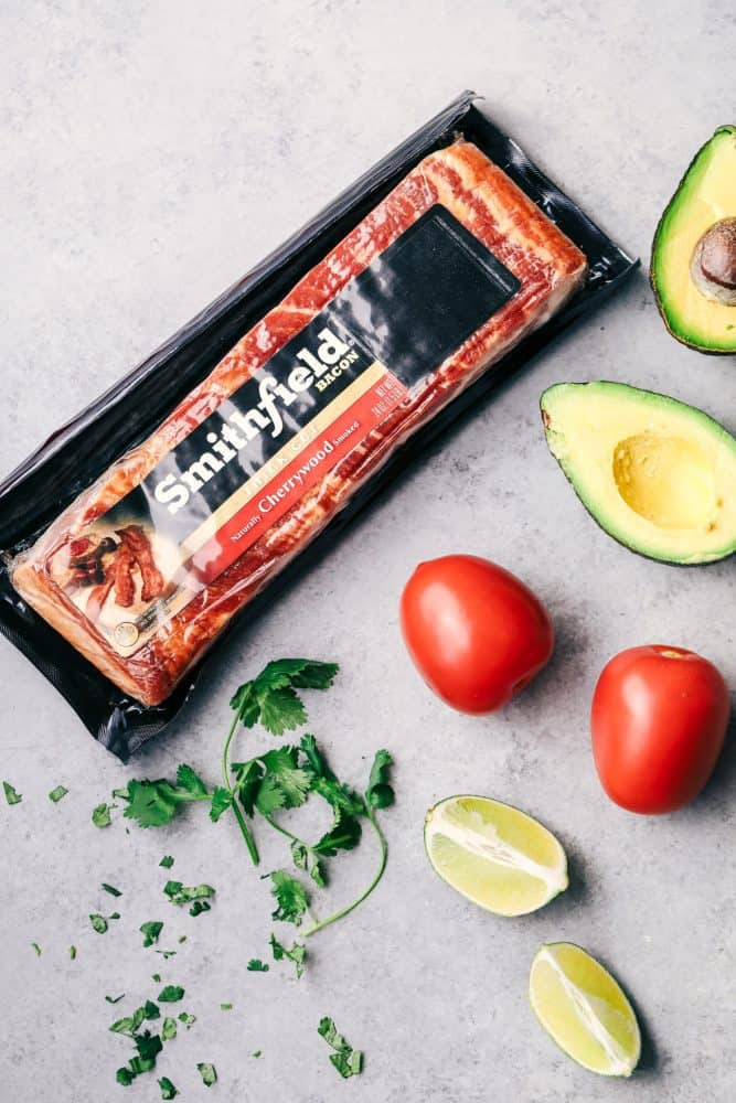 Packaged Smithfield Bacon, slices limes, cherry tomatoes, and sliced avocado.