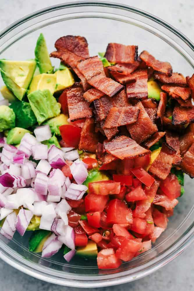 Ingredients for Bacon Guacamole in a clear bowl.