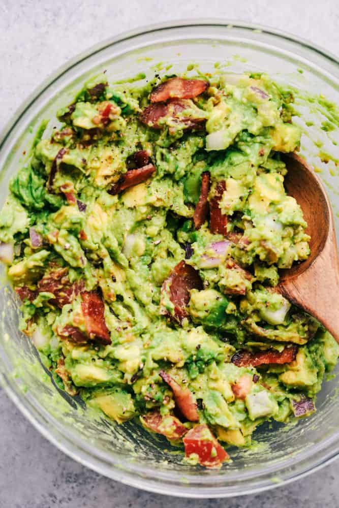 Bacon Guacamole in a white bowl with a wooden spoon.