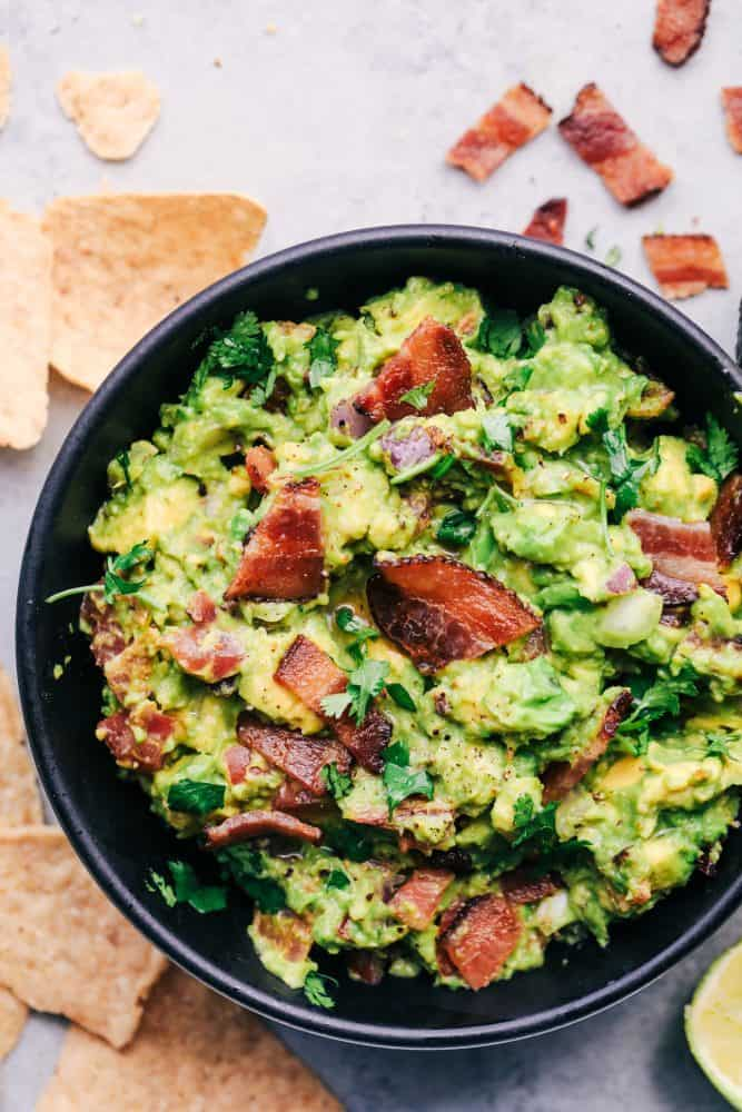 Bacon Guacamole in a black bowl with tortilla chips and bacon bits on the side.