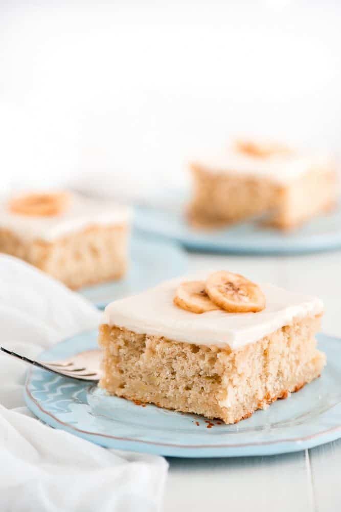 Banana Cake with Cream Cheese Frosting on a light blue plate with a metal fork.
