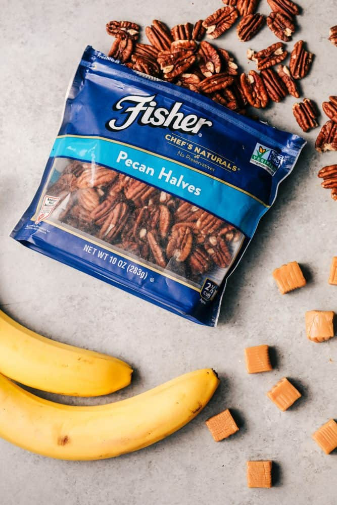 An open bag of pecan halves with two whole bananas and caramels.