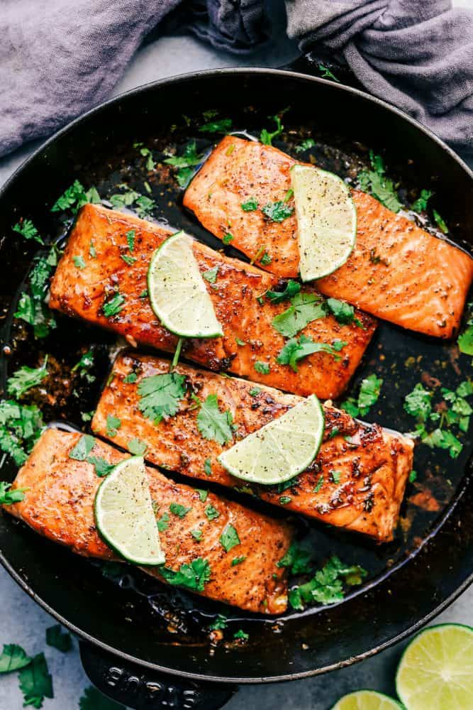 Cilantro Lime Butter Salmon in a skillet with sliced lime on top of the salmon.