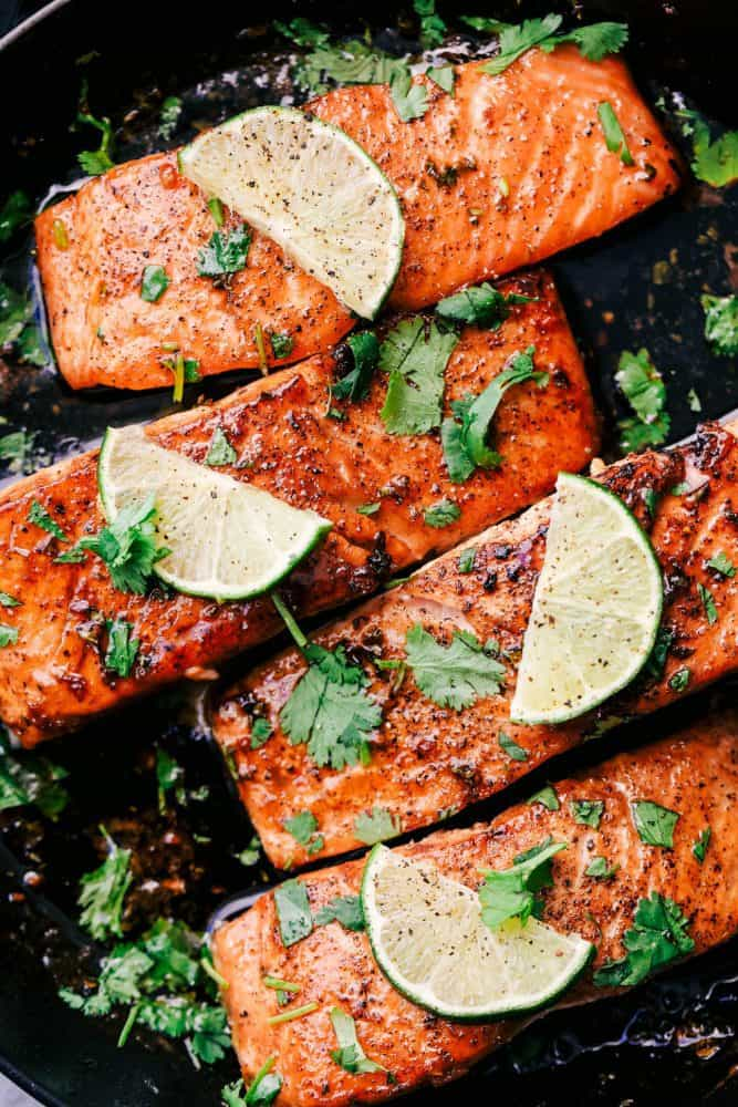 Cilantro Lime Butter Salmon in a skillet with sliced lime on top.
