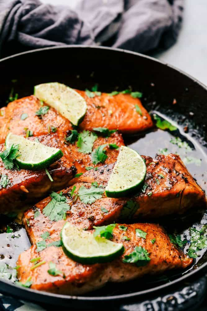 Cilantro Lime Butter Salmon in a skillet with sliced limes on top of the salmon.