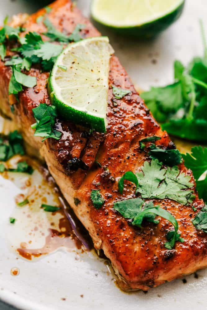 Cilantro Lime Butter Salmon on a white plate with sliced lime on top.