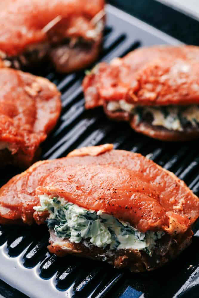 Uncooked herb stuffed pork chops on a grill pan.