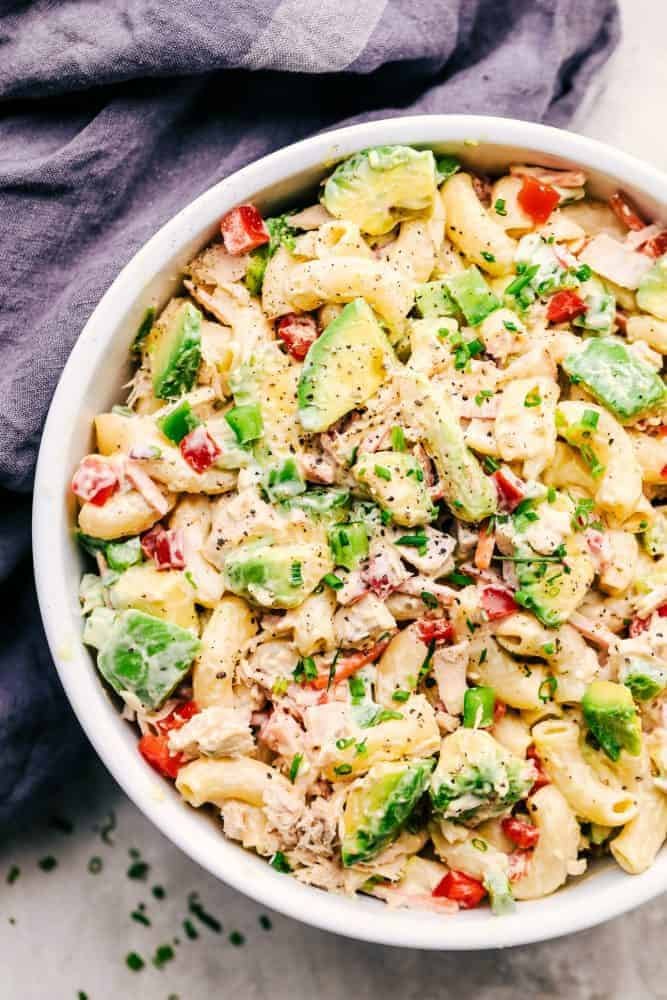 Tuna Avocado Macaroni Salad in a white bowl with a grey cloth on the side.