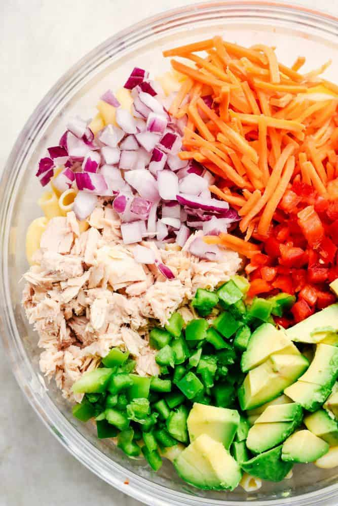 Ingredients for Tuna Avocado Macaroni Salad in a clear bowl.