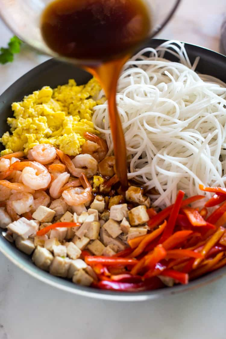 A skillet with the ingredients for Pad Thai including rice noodles, shrimp, scrambles eggs, bell pepper and pad thai sauce being poured on top.