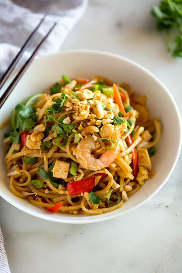 A bowl full of pad thai with rice noodles, shrimp, chicken, tofu, green onion, peanuts and scrambled egg.