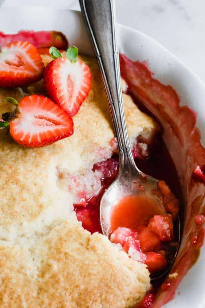 Strawberry Cobbler with a spoonful removed and fresh cut strawberries on top.