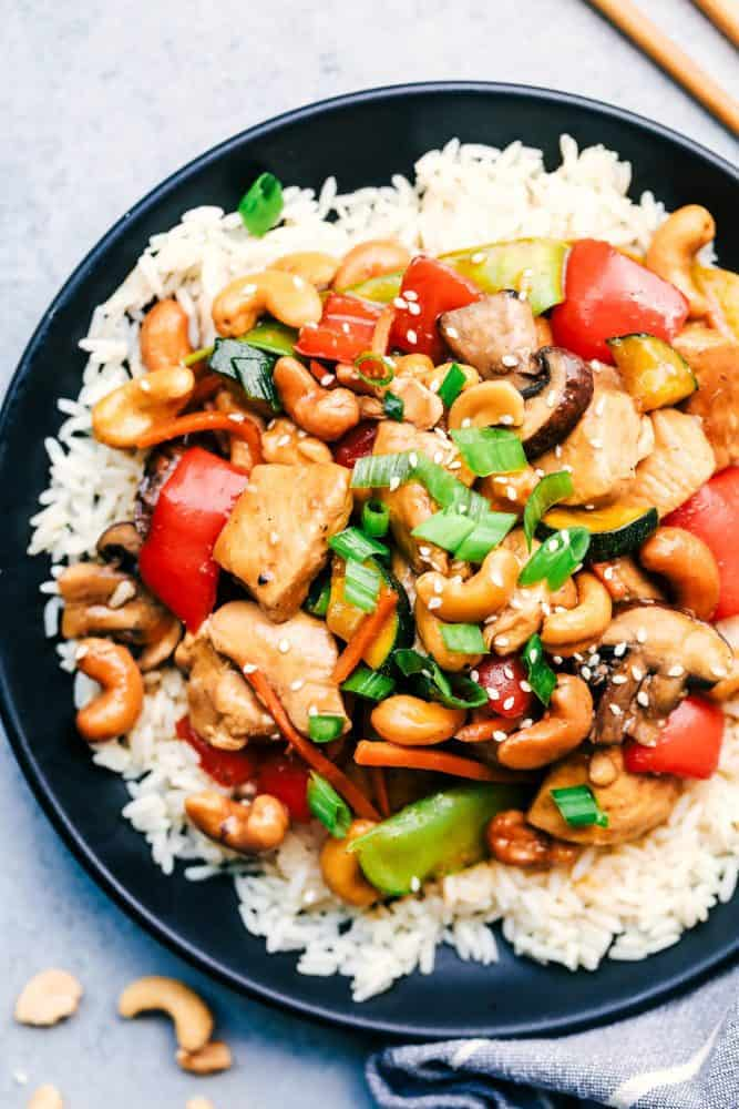 Cashew Chicken Stir Fry over white rice in a black bowl.