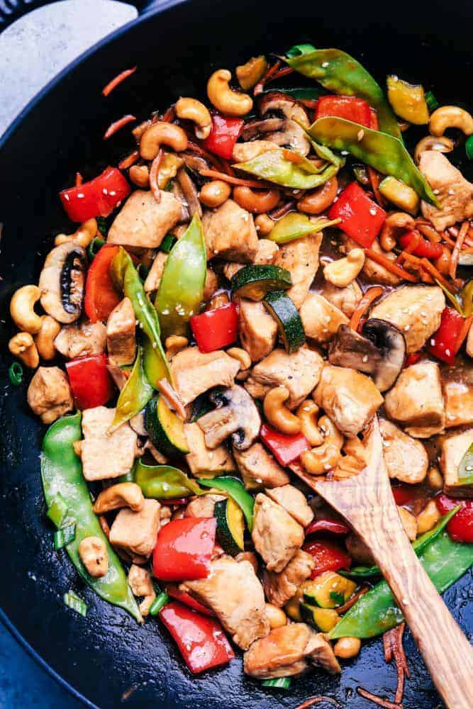 Cashew Chicken Stir Fry in a fry pan with a wooden spoon.