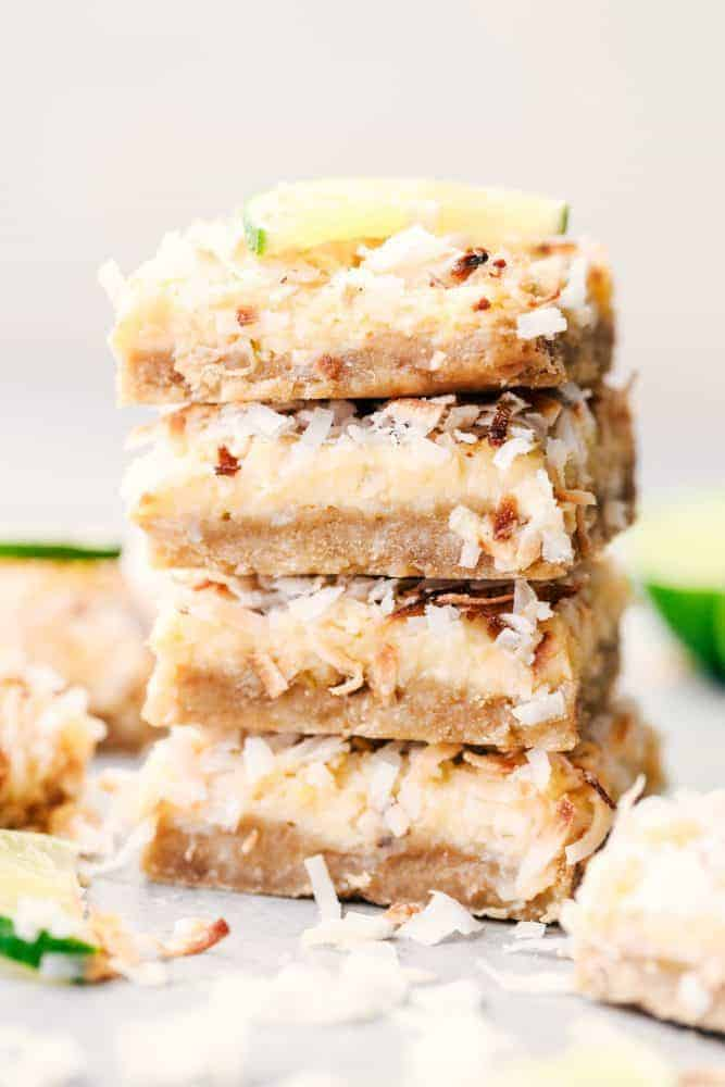 Four Coconut Lime Butter Bars stacked on top of each other with a fresh sliced lime on top.