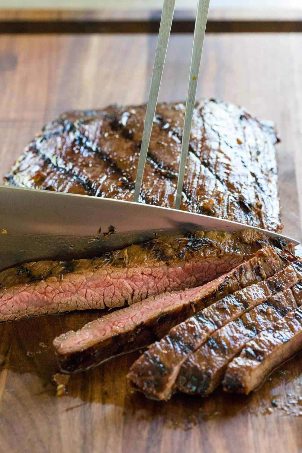 Knife slicing flank steak into strips on a cutting board