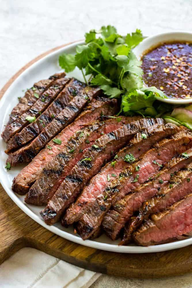 strips of grilled flank steak on a plate served with sauce.