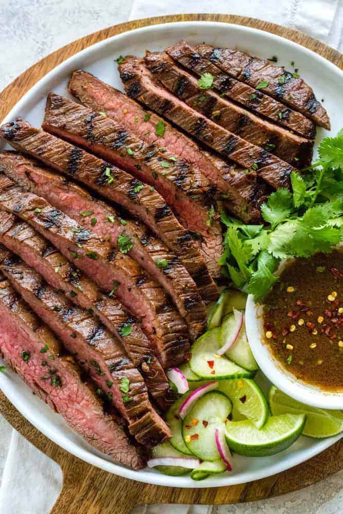 Grilled flank steak with pickled cucumbers on a plate.