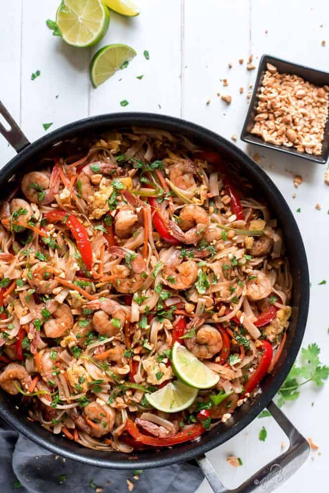 Shrimp Pad Thai in a black skillet with peanuts and sliced lime on the side.