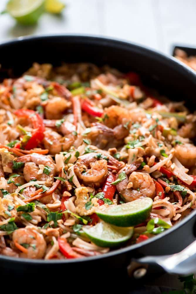 Shrimp Pad Thai in an iron skillet with freshly sliced lime on the side.
