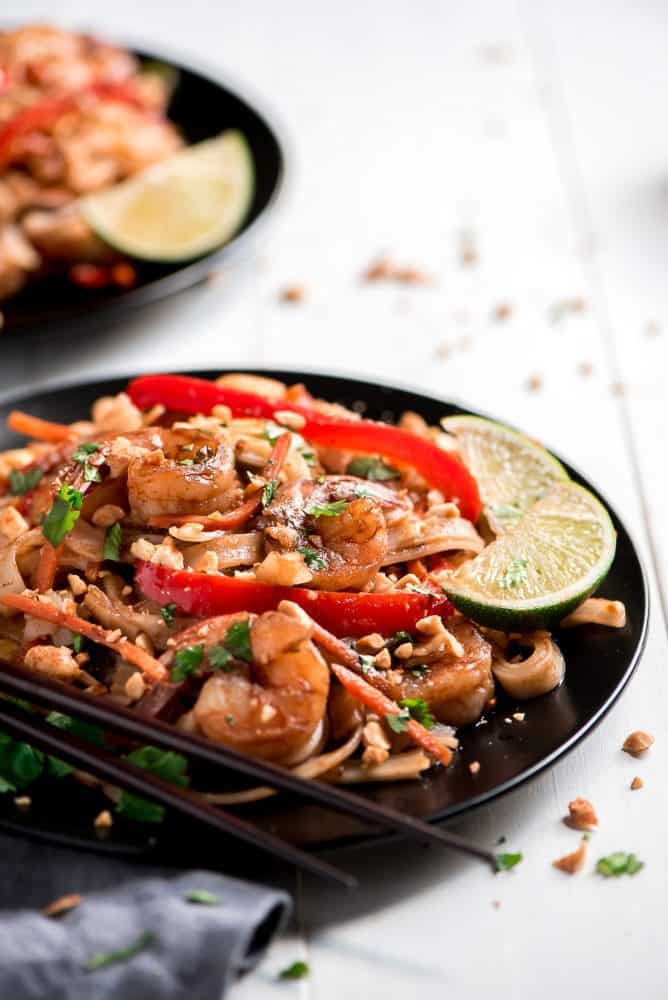 Shrimp Pad Thai on black plats with chop sticks and fresh limes on the side.
